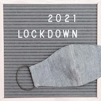 메시지 텍스트 잠금 2021 및 회색 천 보호 안면 마스크가있는 flatlay 문자 보드. 로딩 개념을 잠급니다.