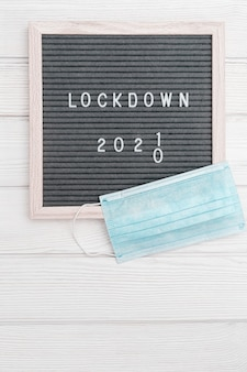 Flatlay letter board with message text lockdown  and grey cloth protective face mask lock down loading concept