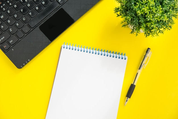 Flatlay mockup of laptop, green plant, pen and notepad on bright yellow background. planning concept with space for text