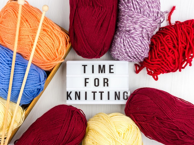 Flatlay of multicolored knitting skeins of yarn and knitting needles with lettering - time to knitting