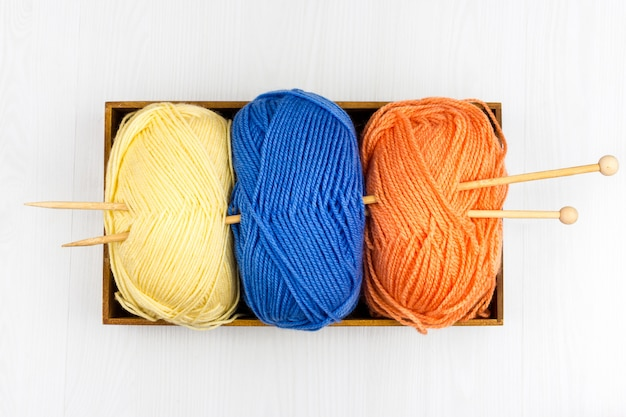 Flatlay of multicolored pastel knitting skeins of yarn and knitting needles on white background
