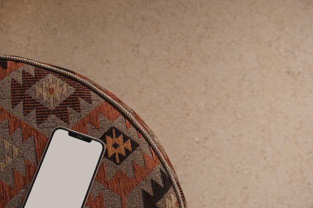 古いカーペットの上に空白の画面の携帯電話のフラットレイ。ホームオフィスデスクワークスペース。