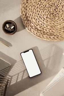 空白の画面のスマートフォン、ノートブック、木製のボウルのクリップ、ベージュのコンクリート表面にストロースタンドのフラットレイ