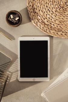 空白の画面のタブレット、ノートブック、木製のボウルのクリップ、ベージュのコンクリートの上にストロースタンドのフラットレイ