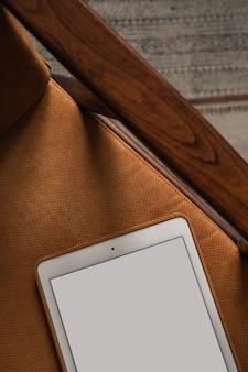 レトロな椅子とカーペットの上の空白の画面のタブレットパッドのフラットレイ。ホームオフィスデスクワークスペース