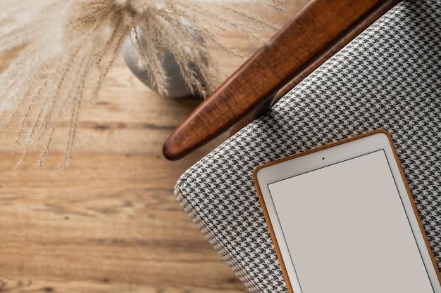 レトロな椅子の上の空白の画面のタブレットパッドのフラットレイ。ホームオフィスデスクワークスペース