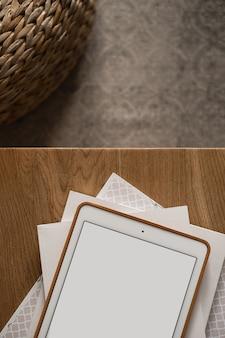 空白の画面のタブレットパッド、木製のテーブルとカーペットの上の紙のシートのフラットレイ。ホームオフィスデスクワークスペース