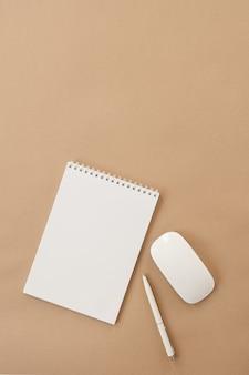 パステルベージュのテーブルに白紙のスパイラルノート、マウス、ペンのフラットレイ