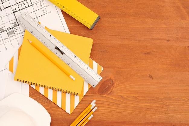 Планировка тетрадей, линейок и карандашей по развернутым чертежам с эскизами нового здания, нарисованными современным инженером