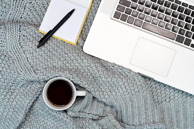 따뜻한 스웨터 커피, 노트북, 노트 패드와 함께 아늑한 작업 쓰기 장소의 flatlay. 집에서 일하십시오. 쓰기.