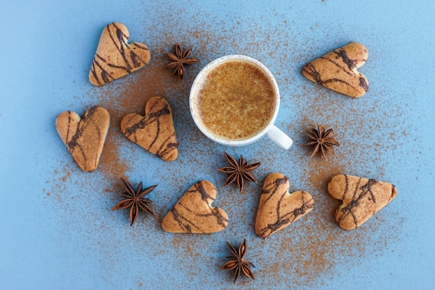 갈색 쿠키와 스타 아니스 근처에 계피로 양념한 커피 한 잔