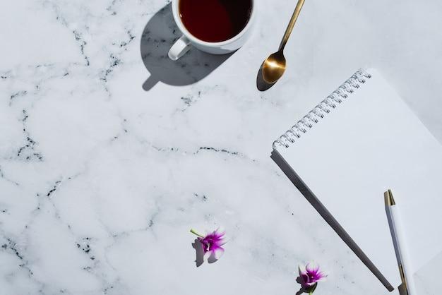 Блокнот с пустой страницей и ручкой на мраморе