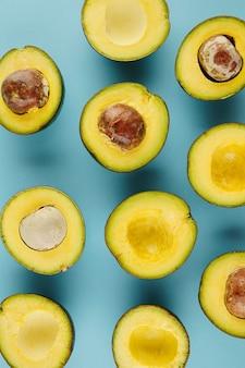 ピットがある場合とない場合のカットアボカドのフラットレイ。夏、食べ物、健康的な食事の概念