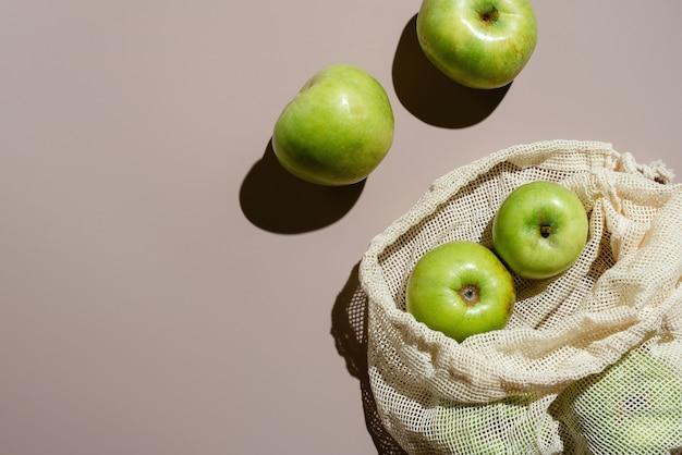 コピースペース付きの綿ゼロ廃棄物メッシュバッグの緑の有機リンゴのフラットレイ、