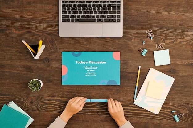 파트너와 회의 작업을하기 전에 노트북 앞에 나무 테이블에 앉아 파란색 형광펜으로 젊은 사업가의 손에 flatlay