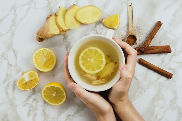 Безалкогольный напиток с лимоном, свежим корнем имбиря, палочками корицы и сиропом агавы на мраморном фоне, от простуды или боли в горле