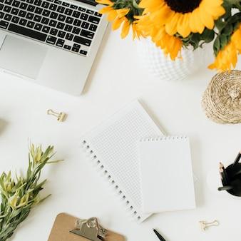 ノートパソコン、ノートブック、白の黄色いヒマワリの花束とホームオフィスデスクワークスペースのフラットレイ