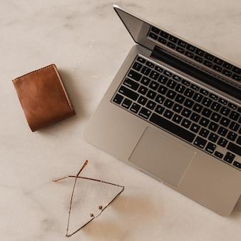 大理石のテーブルの上のラップトップ、財布、グラスのフラットレイ。ホームオフィスデスクワークスペース