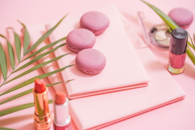 ノートブック、ケーキのマカロン、ピンクのテーブルの花のflatlay。マカロンと美しい朝食