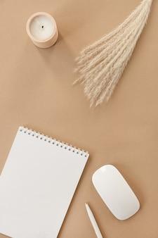 빈 종이 시트와 나선형 플립 노트북의 flatlay. 팜파스 잔디, 베이지 색 복숭아 파스텔 배경 테이블에 편지지.