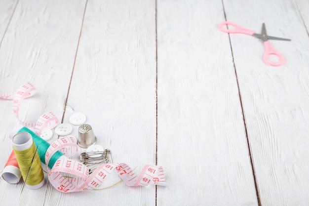 Flatlay инструментов для пошива и рукоделия на белом фоне деревянные