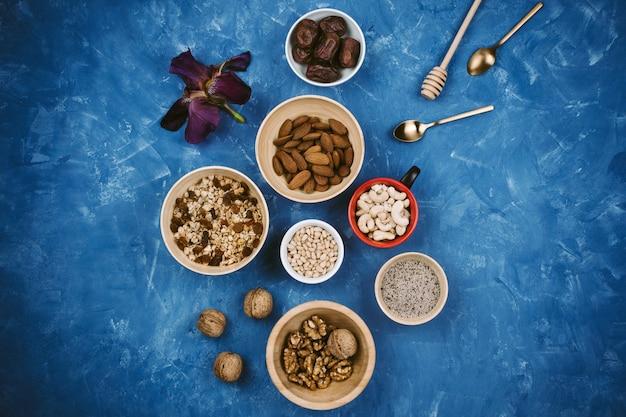 さまざまな種子、ナッツ類、青の背景にボウルにグラノーラのflatlay