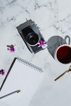 Плоский винтажный пленочный фотоаппарат и блокнот с ручкой на мраморе