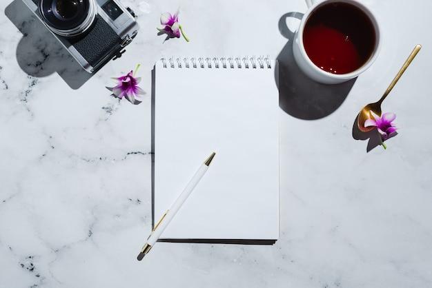 Плоский винтажный чай с пленочной камерой и блокнот с ручкой на мраморе