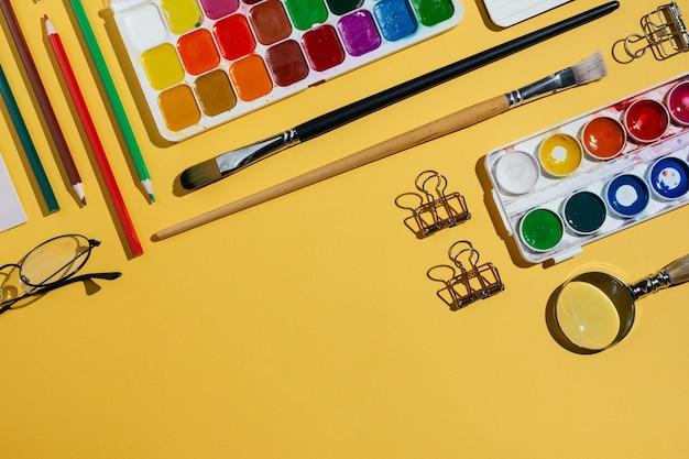 黄色の水彩、ブラシ、ノート、その他の文房具、画材のフラットレイ