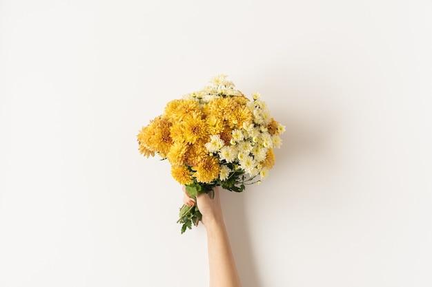 黄色と生姜のフラットレイは、白い背景で隔離の女性の手で野生の花の花束を落ちる。フラットレイ