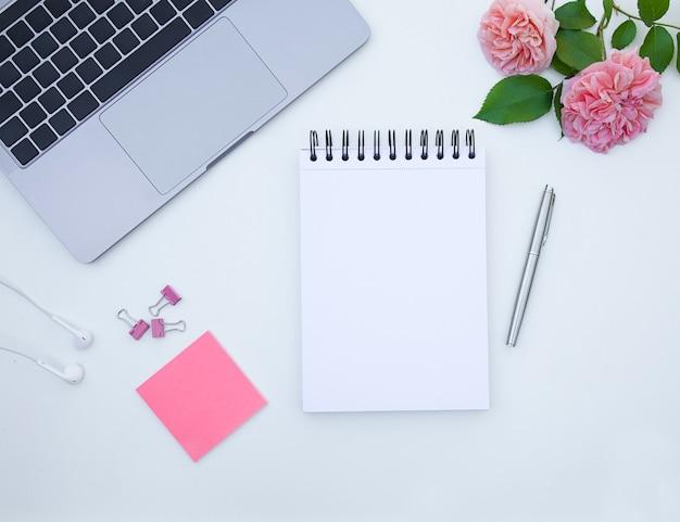 Flatlayオフィスデスクバラのラップトップとブロックノートのある職場計画書のコンセプト
