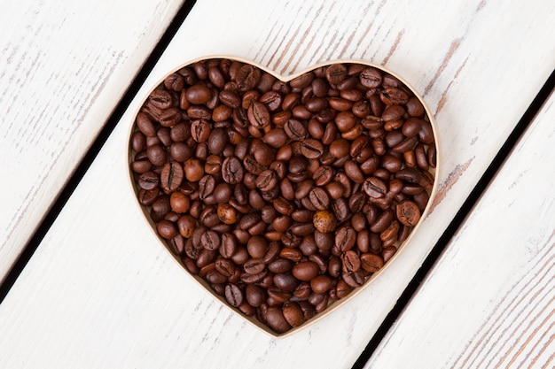 Flatlay photo of heart shaped coffee beans. white planks on surface.