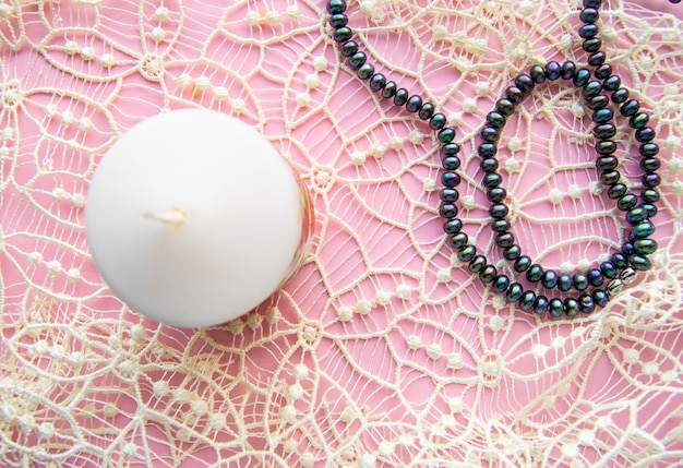 Flatlay pink background, graceful white expensive lace and elegant black pearl with candle, romantic style