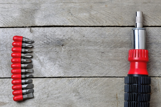 Flatlay.screwdriverと木製のテーブルのビット。コピースペース