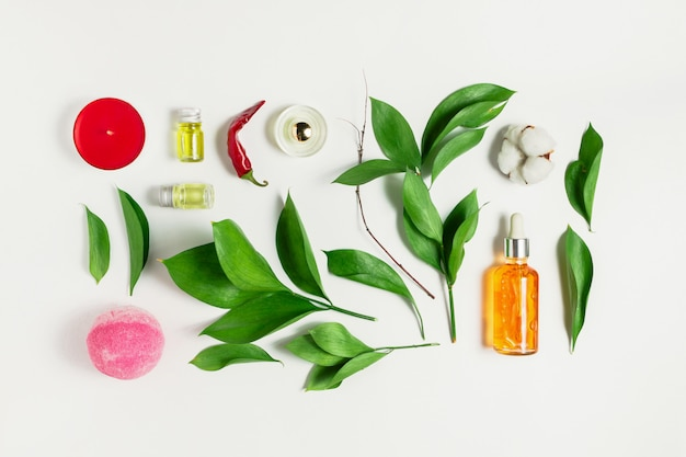 Flatlay of serum, perfume, bath bomb, essential oils with ruscus leaves, pepper and cotton flower on white as a concept of natural body and skincare