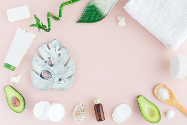 Flatlay of spa cosmetic with bamboo, salt for bath, cream and towel on pastel pink, top view mock-up