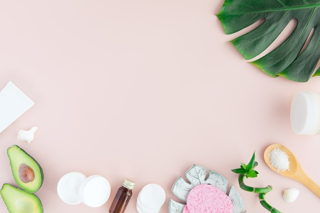 Flatlay of spa cosmetic with bamboo, salt for bath, cream and towel on pastel pink