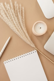 Flatlay of spiral flip notebook with blank paper sheet. laptop, pampas grass, stationery on beige peachy pastel background table.