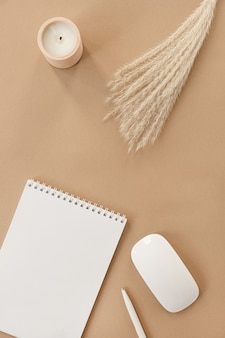 Flatlay of spiral flip notebook with blank paper sheet. pampas grass, stationery on beige peachy pastel background table.