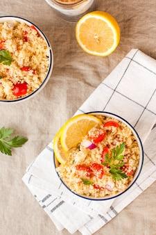 Flatlay taboulehは、クスクス、トマト、パセリで作られたアラビアのベジタリアンサラダです。