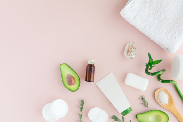 Flatlay and top view of avocado, avocado oil, white towel, jar of cream, green leaves and bamboom avocado on pastel pink