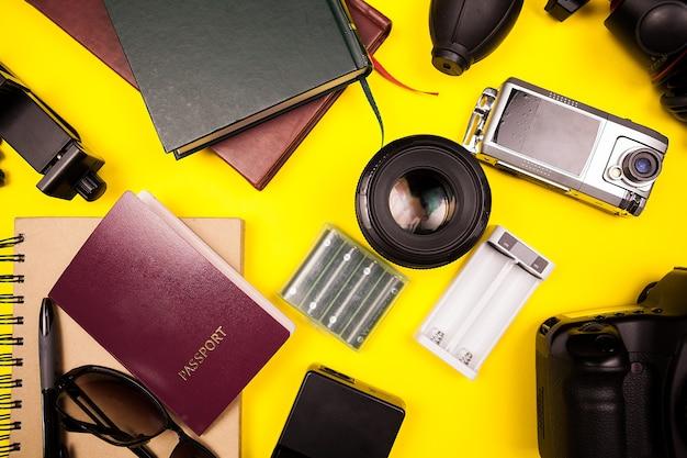 Вид сверху flatlay комплекта путешественника на желтом фоне в фото studiop. рядом с другими аксессуарами паспорт, книги, фотоаппарат с объективом, бумага и солнцезащитные очки.