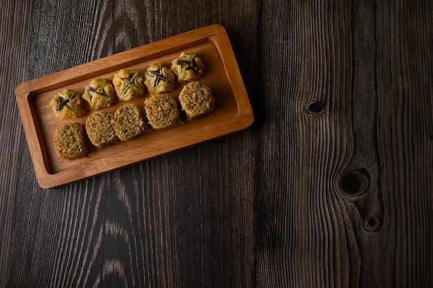 Сладкое тесто flatlay турецкая пахлава на деревянном подносе традиционные десерты из турции