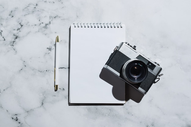 Flatlay of vintage film camera and notebook with pen on marble