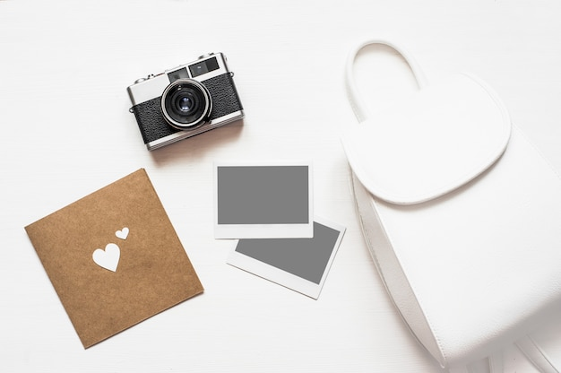 Flatlay vintage retro camera on wooden white background with empty instant paper photo