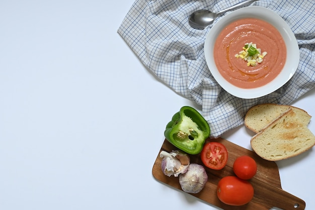 Flatlay of white plate with spanish cordovan salmorejo gazpacho next to dark wood table with tomato, green pepper, garlic and toast, on a checkered tablecloth and a white surface, with copy space