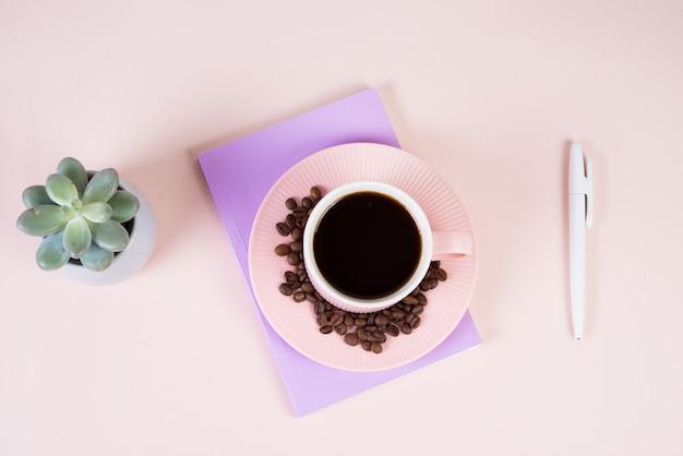 テーブルの上のブラックコーヒーのカップ、メモ帳、セラミックポットにジューシーなフラットレイ。デスクトップ、ビジネス、パステルカラー