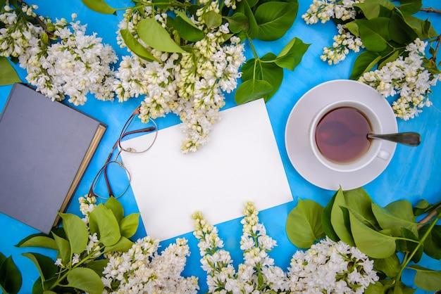Flatlay с ветками белой сирени, книга, стаканы и чай