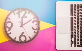 Flatlay with clock and keyboard on three tone solid color yellow, violet and light blue