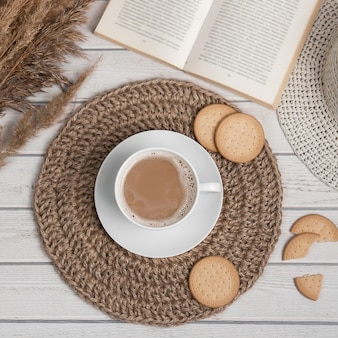 Flatlay with cup of americano or espresso jute mat cookies and book on white wooden table.